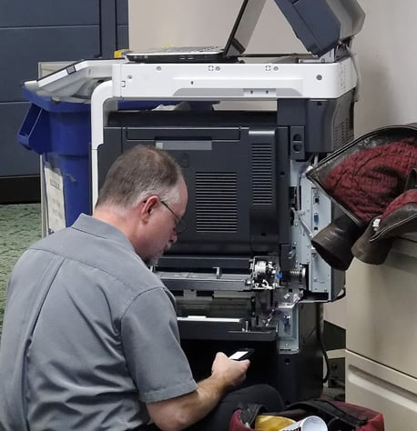 man repairing an office printer